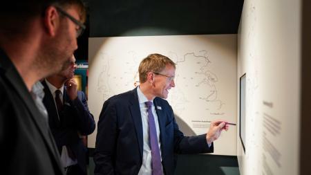 Zwei Männer blicken auf eine Ausstellungstafel.