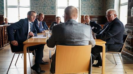 Sechs Männer sitzen an einem großen Tisch und unterhalten sich.
