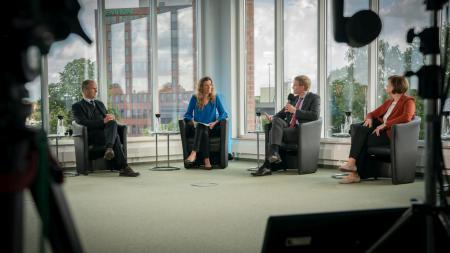 Ministerpräsident Daniel Günther sitzt mit mehreren Männern und Frauen in einem Fernsehstudio und diskutiert mit ihnen.