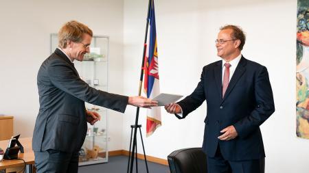 Ein Mann übergibt eine Urkunde an einen anderen Mann.