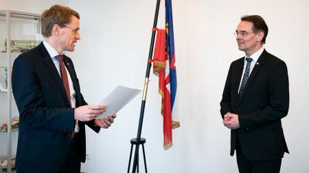 Ministerpräsident Daniel Günther steht vor Ingbert Liebing und liest eine Urkunde vor.