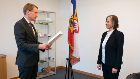 Ministerpräsident Daniel Günther steht vor der Datenschutzbeauftragten des Landes, Marit Hansen, und liest ihr die Ernennungsurkunde vor.