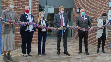 Vier Frauen und zwei Männer, darunter Ministerpräsident Daniel Günther sowie Vertreter des Hospizvereins, der Stadt Gettorf und des Kreises, stehen vor einem neuen Gebäude und schneiden eine blumengeschmückte Girlande durch.