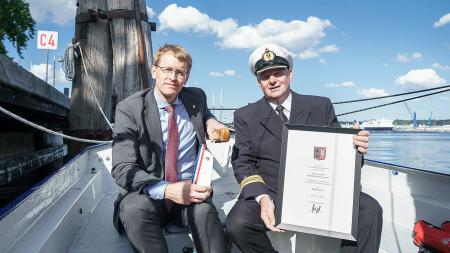 Ministerpräsident Daniel Günther und Kapitänleutnant Thomas Geburzky sitzen nebeneinander in einem Marinekutter und halten die Auszeichnung in den Händen.