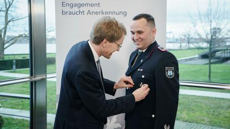 Ministerpräsident Daniel Günther heftet Adrian Jensen einen Orden an die Brust.