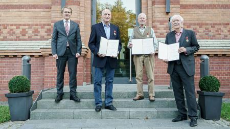 Vier Männer stehen auf der Treppe vor einem Gebäude, drei halten Dokumente in den Händen.