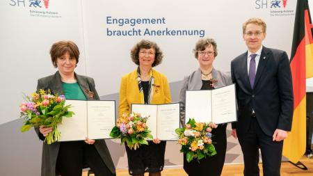 Minsterpräsident Daniel Günther und drei Frauen stehen zusammen, die Frauen halten Blumensträuße und Urkunden in den Händen.