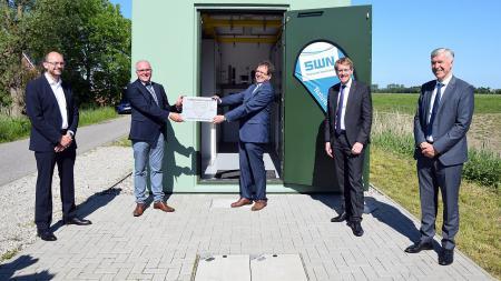Zwei Männer halten im Beisein von Ministerpräsident Daniel Günther eine Plakette in die Höhe.