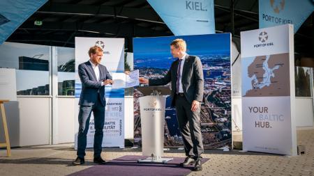 Zwei Männer tauschen ein Dokument aus. Im Hintergrund sind Banner auf denen Port of Kiel steht.