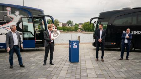 Ministerpräsident Daniel Günther steht neben Vereinsvertretern von THW Kiel und Flensburg-Handewitt und hält die Meisterschale in der Hand.