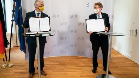 Ministerpräsident Daniel Günther (r.) und Hinrich Jürgensen, Hauptvorsitzender des Bund Deutscher Nordschleswiger bei der Unterzeichnung in Kiel.