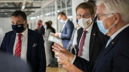 Ministerpräsident Daniel Günther und Frank-Walter Steinmeier unterhalten sich mit einem Vertreter von Dräger.