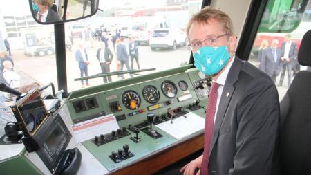 Ministerpräsident Daniel Günther sitzt in einer Lokführer-Kabine. Er trägt eine Mund-Nasen-Bedeckung und lächelt in die Kamera.