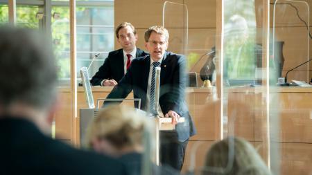 Ministerpräsident Daniel Günther steht am Rednerpult im Landtag.