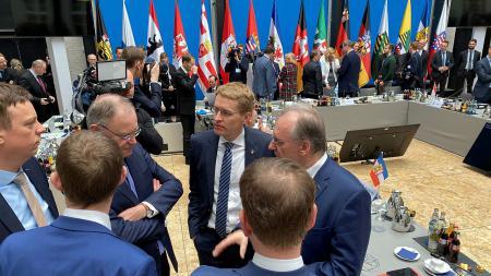 Ministerpräsident Daniel Günther im Gespräch mit sechs weiteren Männern.