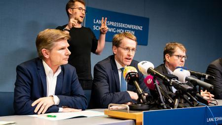 Ministerpräsident Daniel Günther, Gesundheitsminister Garg und Oppositionsführer Ralf Stegner sitzen an einem Tisch. Vor ihnen sind Mikrofone aufgebaut
