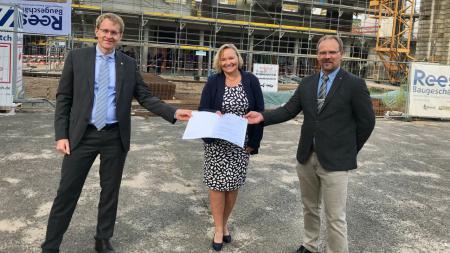 Ministerpräsident Daniel Günther überreicht einen Förderbescheid an Schulverbandsvorsteherin Beate Nielsen und Schulleiter Sven Gritto. Hinter ihnen befindet sich eine große Baustelle.