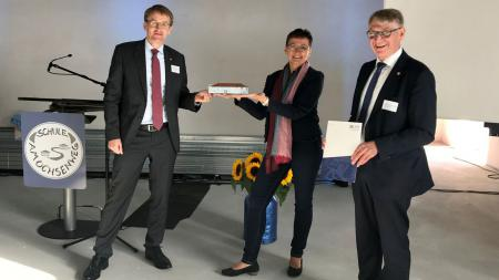 Ministerpräsident Daniel Günther hält ein Modell eines Gebäudes in der Hand und überreicht es an die Schulleiterin der Schule am Ochsenweg, Elke Fooken-Verweyen. Neben ihnen steht der Vorsteher des Amts Jevenstedt, Hans Hinrich Neve.
