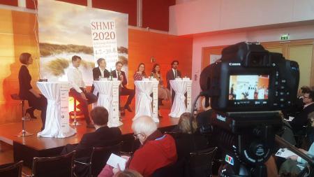 Mehrere Männer und Frauen sitzen auf einer Bühne vor einem Banner des SHMF.