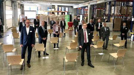 Ministerpräsident Daniel Günther steht gemeinsam mit mehreren Menschen in einer Werkhalle.