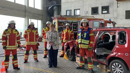 Die Innenministerin im Kreis von Feuerwehrkräften zum Gruppenbild in der Ausbildungshalle.