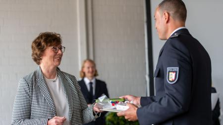 Die Ministerin gratuliert einem Absolventen