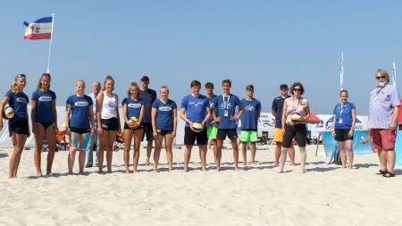 Die Teilnehmerinnen und Teilnehmer stehen mit Verbandspräsident Neppessen und Staatssekretärin Kristina Herbst zu einem Gruppenfoto am Strand.