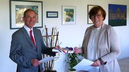 Joachim Albrecht erhält von Sabine Sütterlin-Waack seine Papiere und ein Geschenk.