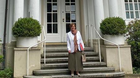 Die Ministerin steht auf Treppenstufen vor dem Gut Glinde.