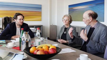 Am Tisch sitzt Minister Albrecht neben zwei Besuchern in seinem Büro.