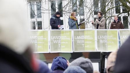 Auf einem Lastwagen stehen vier Personen und sprechen zu Demonstranten.