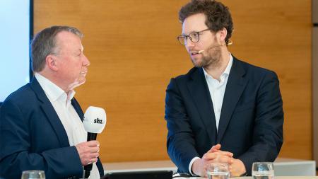 An einem Podium stehend diskutieren zwei Männer miteinander