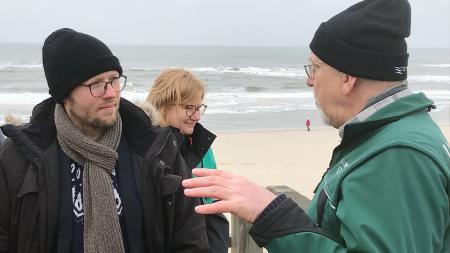 Zwei Herren stehen am Strand und sprechen über Küstenschutz
