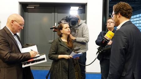 Vor Fernsehkameras gibt Minister Albrecht den Journalisten von Zeitungen und Fernsehen Interviews.
