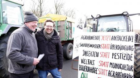 Vor Traktoren unterhalten sich zwei Männer