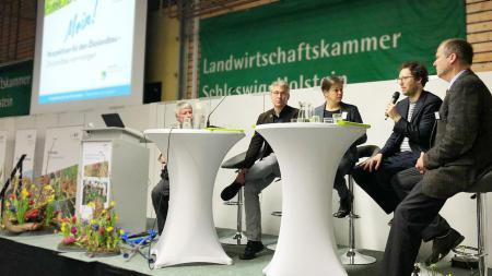 Auf dem Podium sitzen vier Herren und sprechen über Ökolandbau