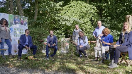 Im Schatten unter Bäumen sitzen Damen und Herren auf Stühlen.