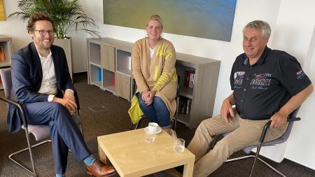Drei Personen sitzen an einem Tisch und diskutieren.