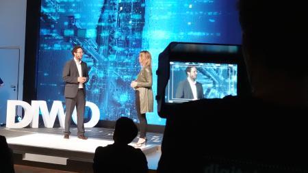 Ein Herr und eine Dame stehen auf dem Podium vor einer Kamera.