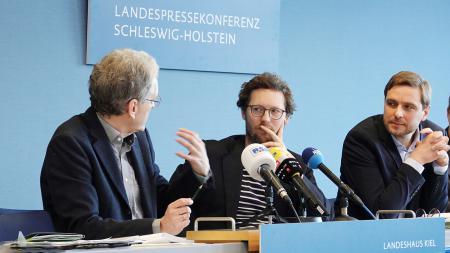 Drei Herren sitzen auf dem Podium und diskutieren.