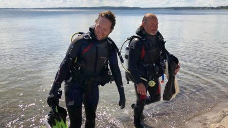Zwei Männer in Taucheranzügen steigen aus dem Meer.