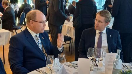 Ministerpräsident Günther und Fürst Albert II. von Monaco sitzen an einem Tisch und führen ein Gespräch.