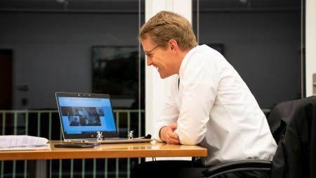 Ministerpräsident Daniel Günther sitzt an einem Tisch in seinem Büro. Auf einem Laptop vor ihm läuft eine Videokonferenz mit mehreren Schornsteinfegern.