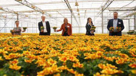 3 Frauen und 2 Männer stehen in einem Gewächshaus inmitten von Blumen. Jeder hält einen oder zwei Blumentöpfe in der Hand.