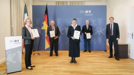 Ministerpräsident Daniel Günther steht neben zwei Männern und zwei Frauen. Diese halten jeder eine Urkunde in der Hand.