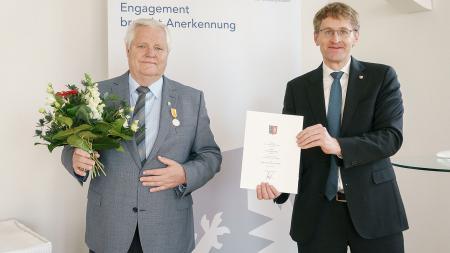 Zwei Männer stehen vor einer Stellwand, einer hält einen Blumenstrauß, der andere eine Urkunden in den Händen.