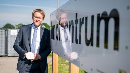 Ministerpräsident Daniel Günther steht neben einem Hinweisschild vom Impfzentrum.