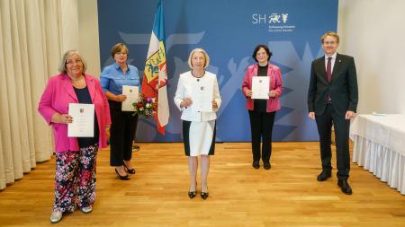 Ministerpräsident Daniel Günther und die Ausgezeichneten stehen nebeneinander. Die Frauen halten Urkunden in den Händen.