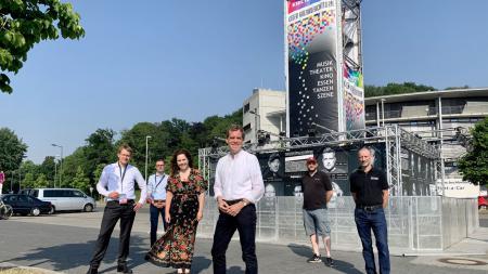 Mehrere Personen stehen vor einem Turm. Darauf steht: Kieler Kultur-Leuchtturm.
