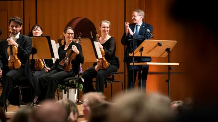 Ministerpräsident Daniel Günther steht neben einem Orchester.